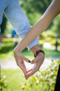 a man and woman slightly holding hands to make a heart with their hands